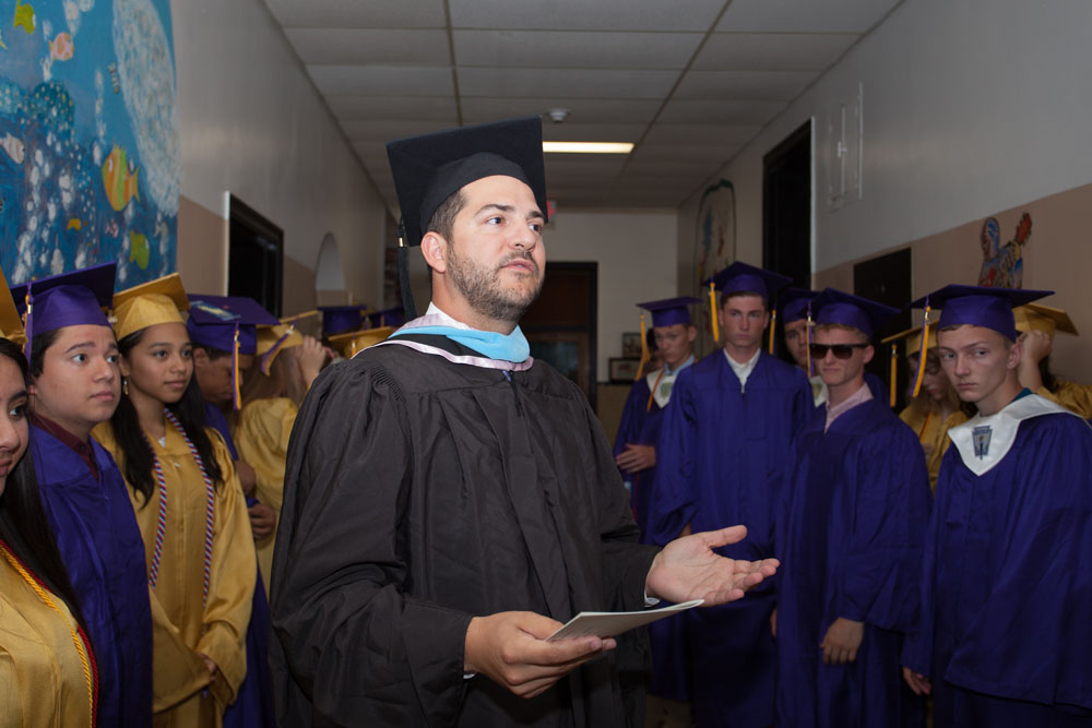 Principal Gary Kalish addresses the graduates in the hallway before the ceremony. (Credit: Katharine Schroeder)