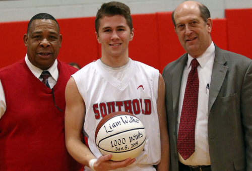 Liam Walker was recognized for recently becoming only the second Southold boy to score 1,000 career points. He was joined by coach Phil Reed, left, and the school superintendent, David Gamberg, in a pregame ceremony in which he was presented with a ball to mark the milestone. (Credit: Garret Meade)