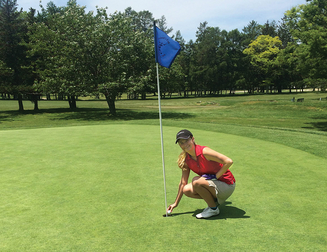 Catherine Brabazon of Greenport picks the ball out of the cup after acing her first hole-in-one on the third hole at Island's End Country Club in Greenport. (Credit: Jay Dempsey)