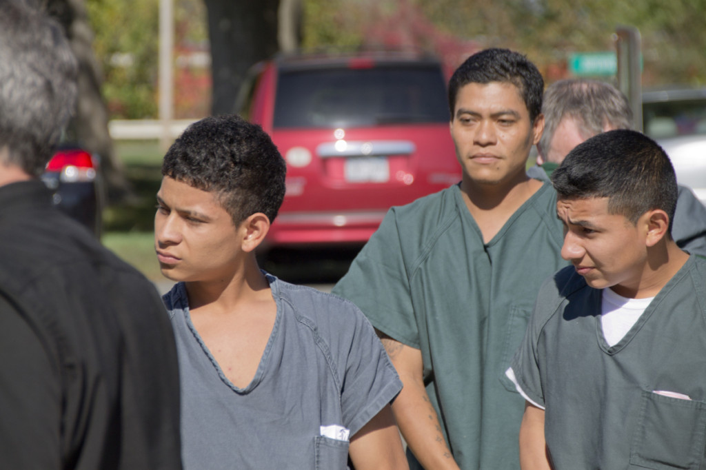 Southold shooting suspects (from left) Walter Vasquez, 17, of Greenport;  Pedro Emilio Santamaria, 31, of Greenport; and Jeremias Nathaniel Recinos Torres, 19, of Aquebogue are escorted by corrections officers into Southold Town Court earlier this year. (Credit: Paul Squire, file)